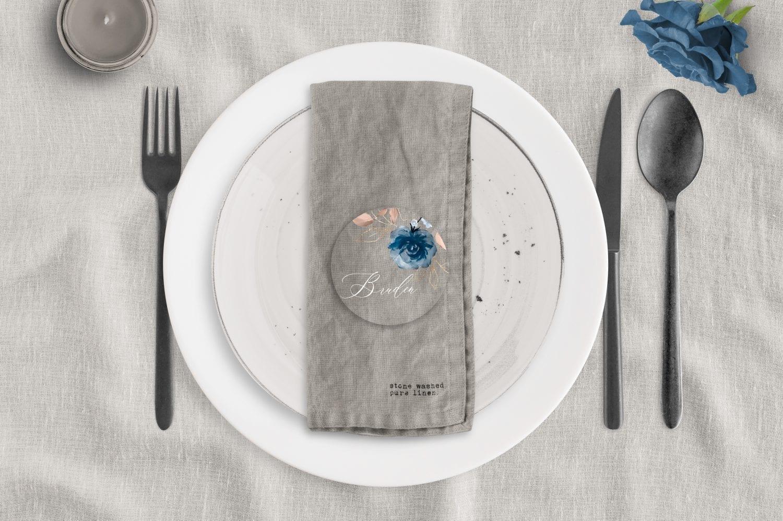 Akryl bordkort med blå blomster på dækket bord med tallerken.